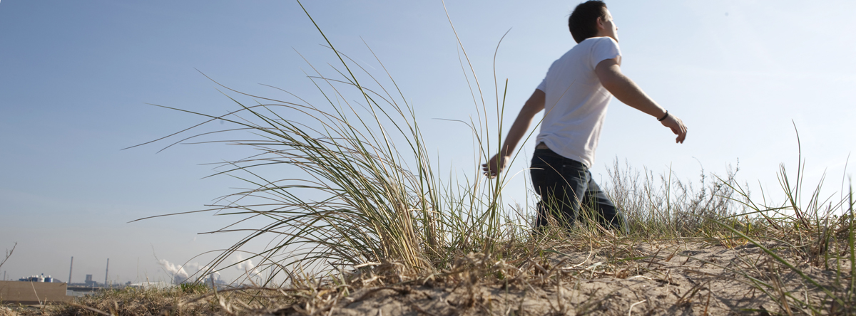 Man walking along sand dune
