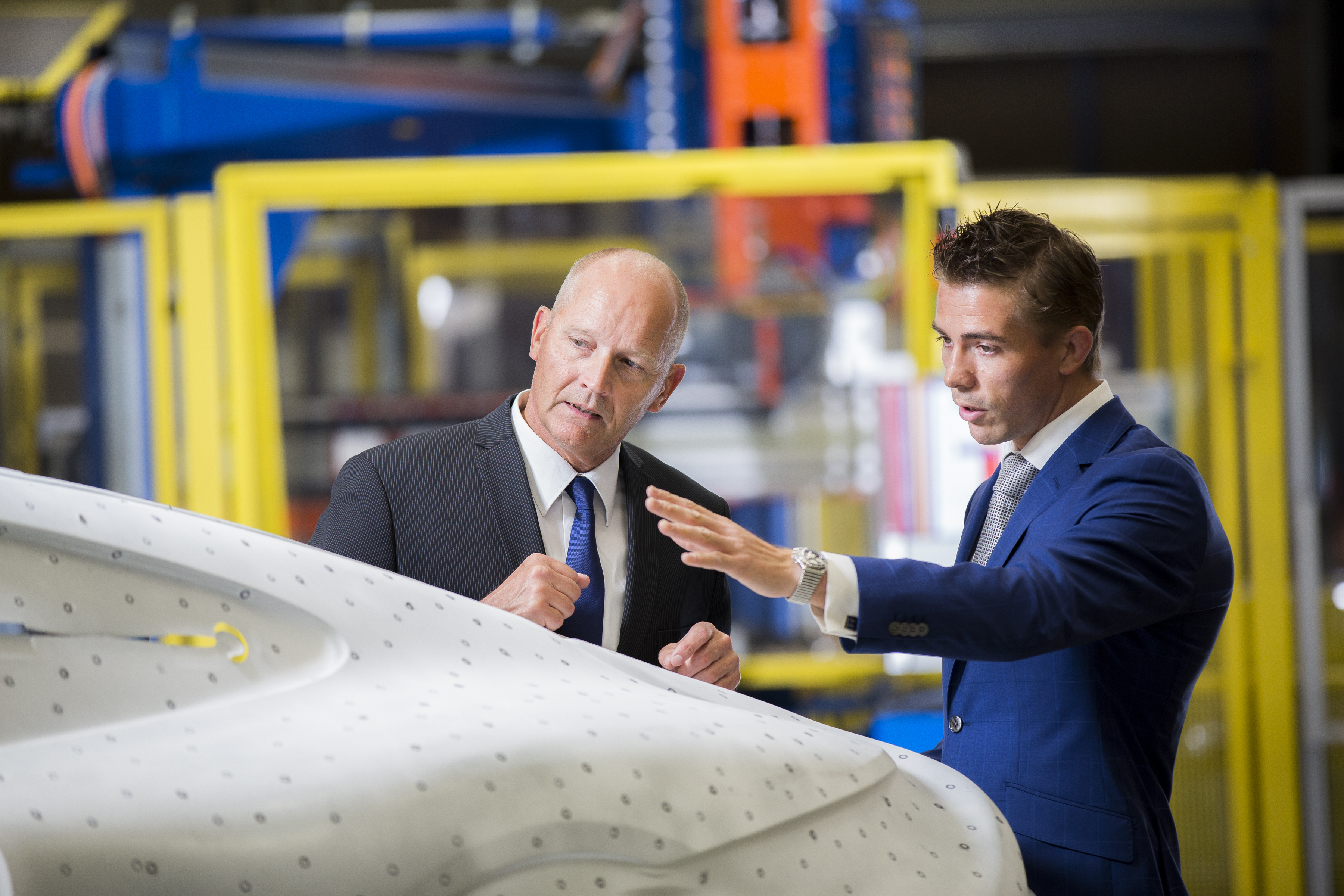 Two business colleagues looking at a car panel, deep in discussion