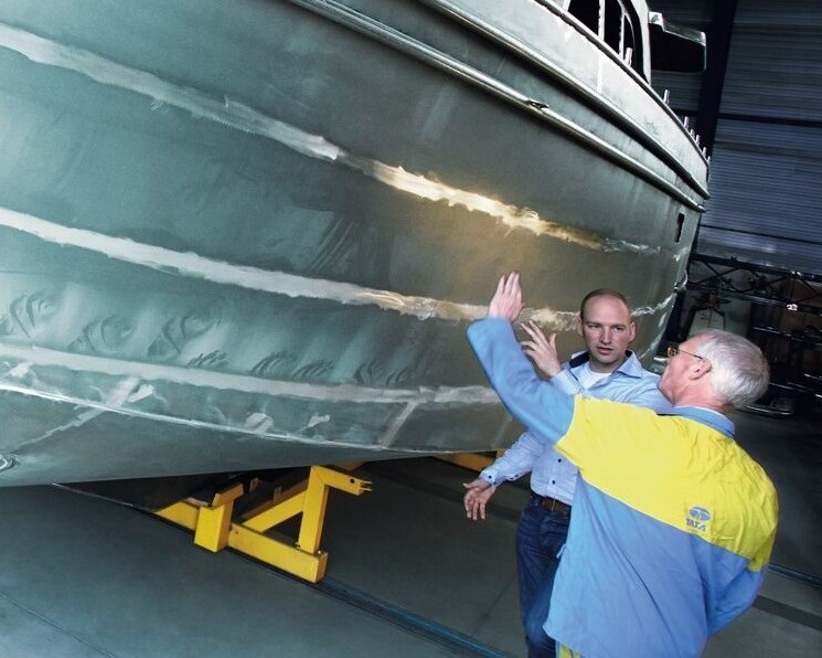 Tata Steel and Linssen workers reviewing the bottom panel of a yacht