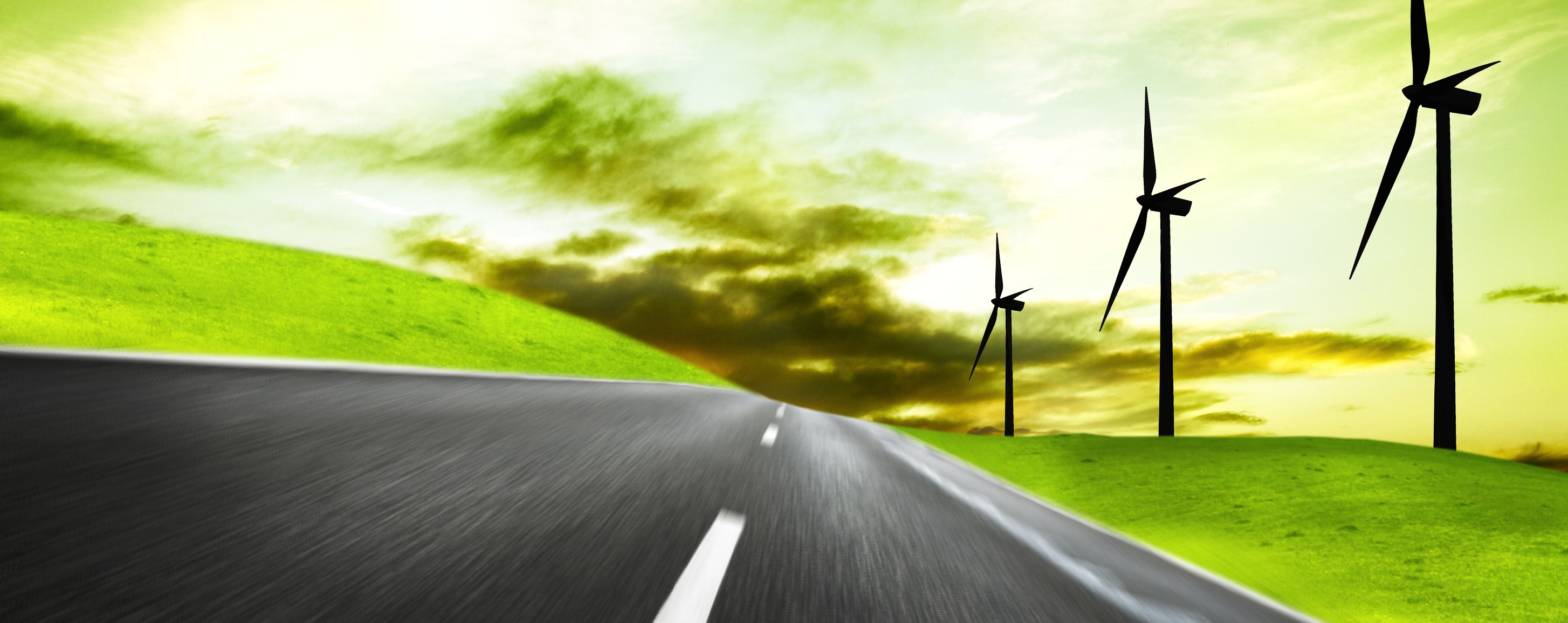 Futuristic picture depicting a road winding the countryside with wind turbines and a green sky