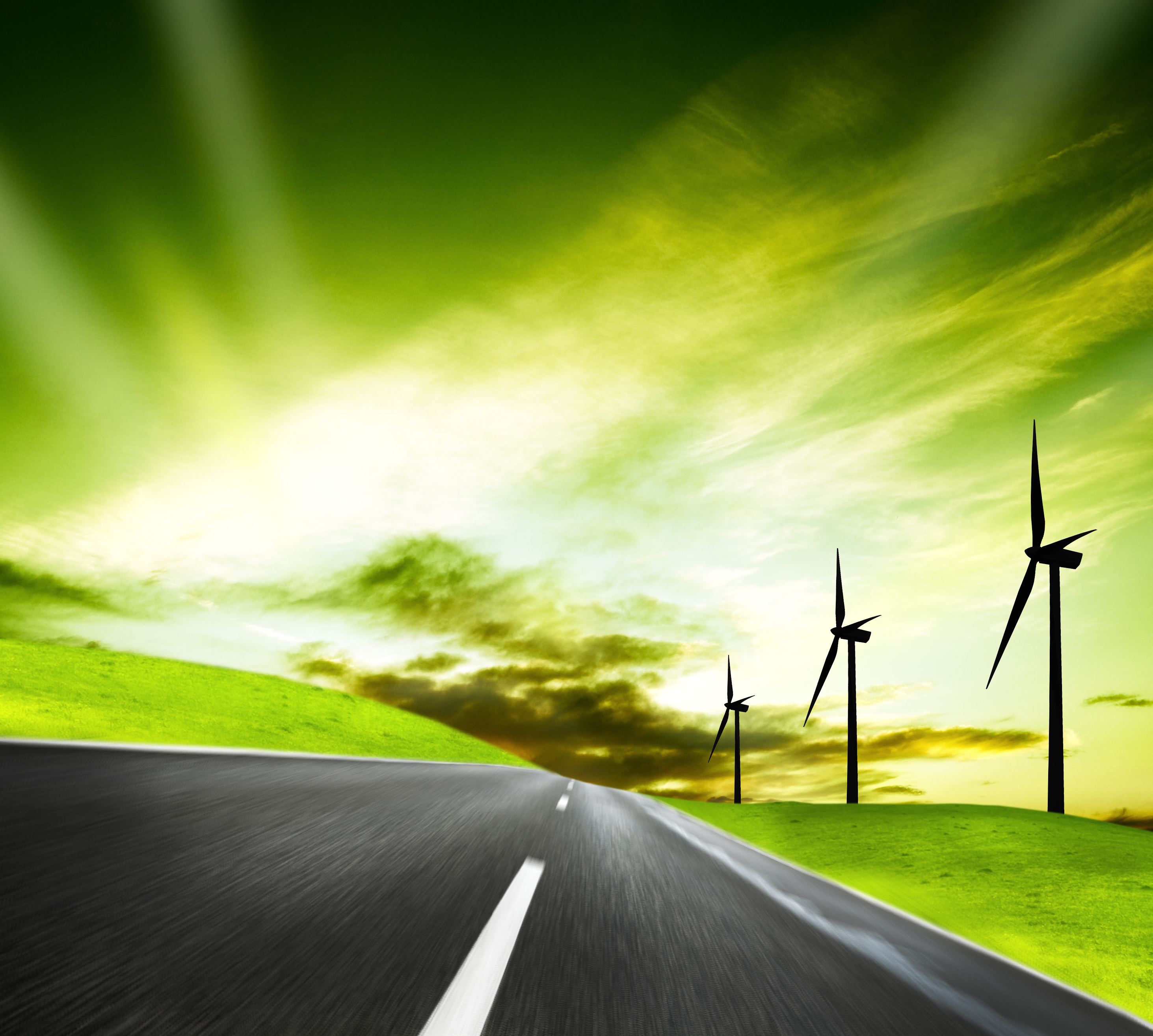 Futuristic view showing a country road with wind turbines on the right side and a green sky