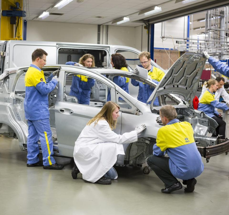 Several Tata Steel technicians working on a car frame