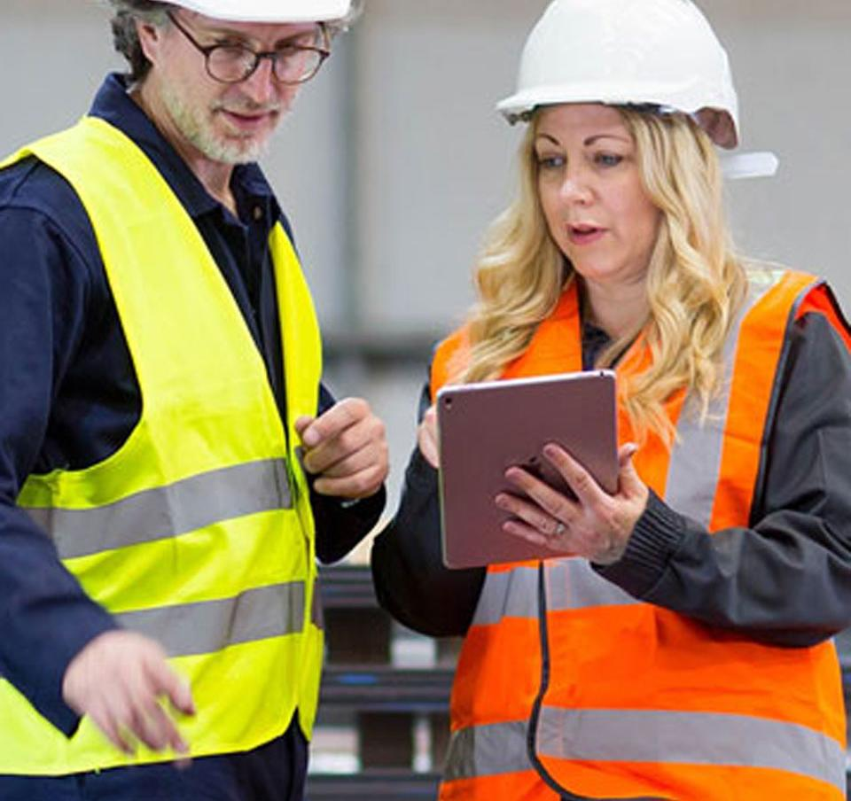 Man and woman wearing hard hats using mobile device for business