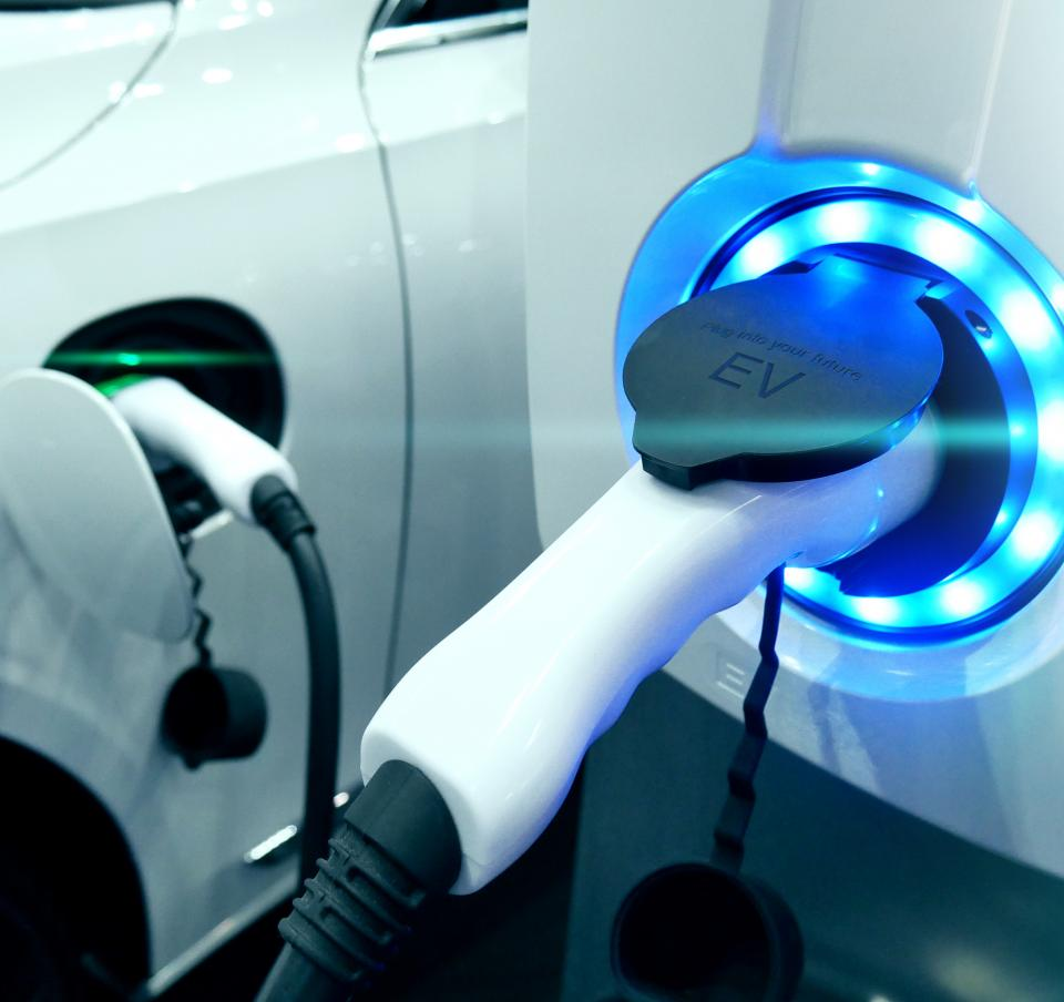 An electric car being charged showing both the charging unit and charging point